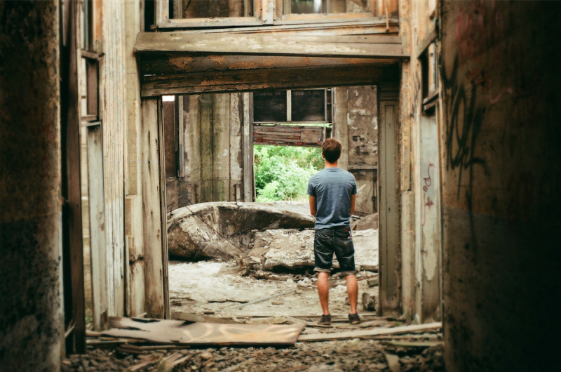 film photography urbex abandoned ruinporn crumbling debris gary indiana union station young man standing doorway chiaroscuro