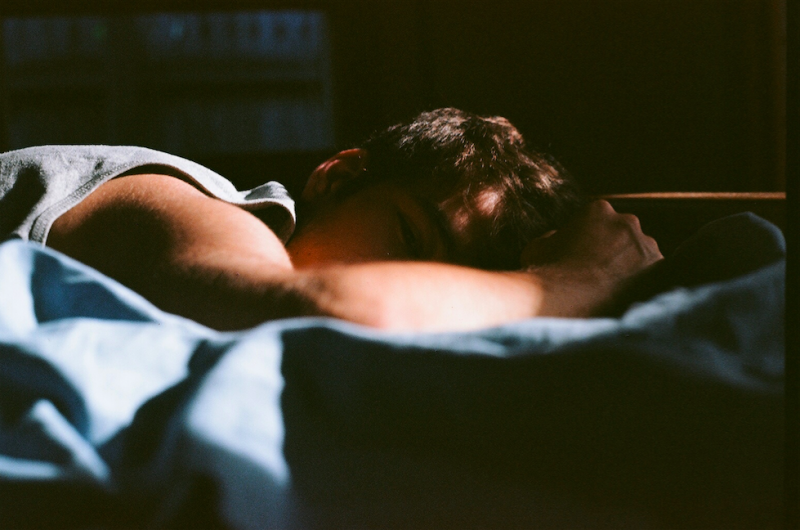 film photograph portrait young man hapa lying bed shadow chiaroscuro