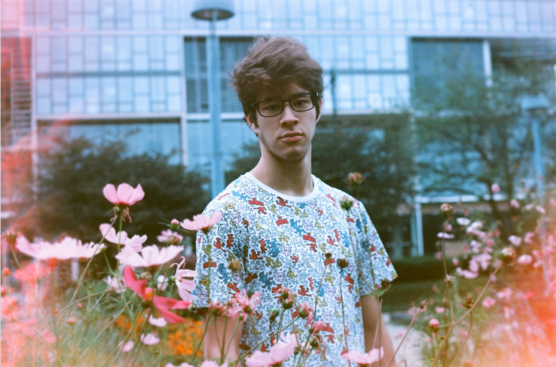 film photograph portrait young man park flowers pink hapa glasses
