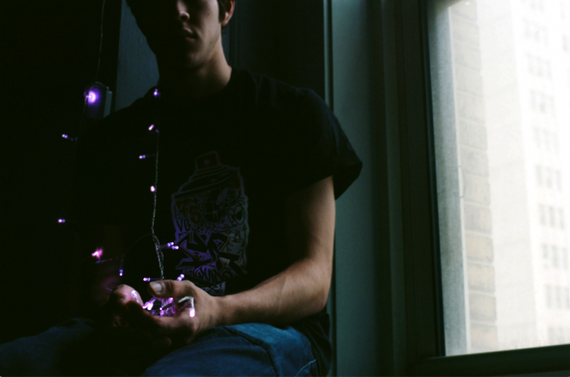 film photograph portrait young man sitting christmas purple light holding string dark shadow chiaroscuro