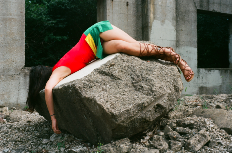 film photograph portrait young woman girl cosplay rubble urbex rock stone robin costume fallen lying mask