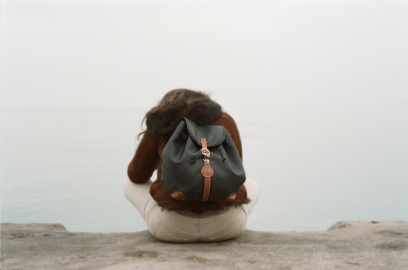 film photograph portrait woman sitting back turned edge of water backpack knapsack