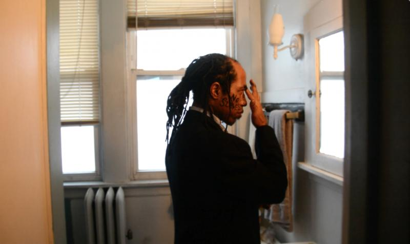 portrait african american man standing in front of the bathroom mirror dreadlocks suit face paint charcoal no slaves