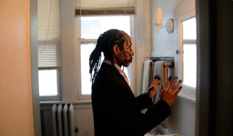 portrait african american man standing in front of the bathroom mirror dreadlocks suit face paint charcoal no slaves hands