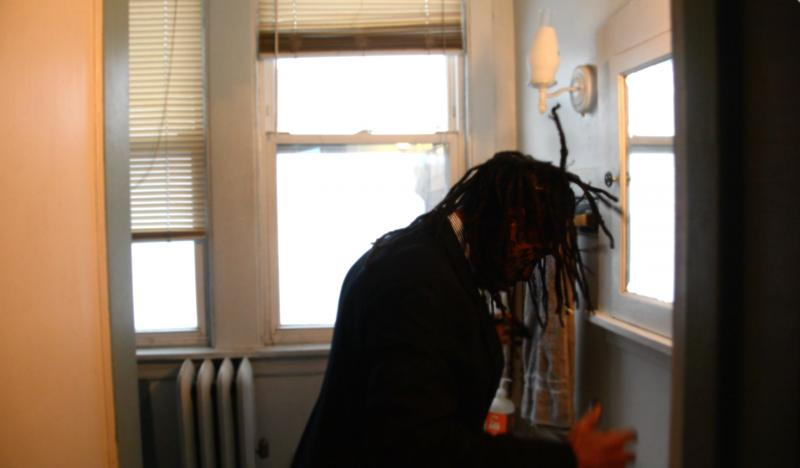 portrait african american man standing in front of the bathroom mirror dreadlocks suit face paint charcoal no slaves swinging hair