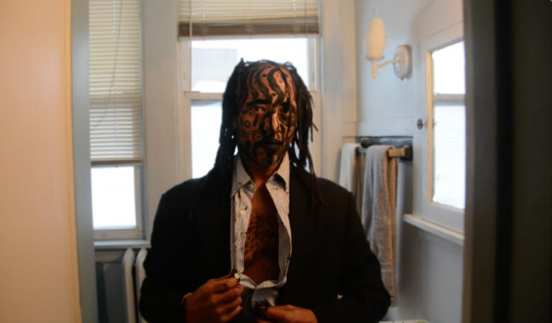 portrait african american man standing in front of the bathroom mirror dreadlocks suit face paint charcoal no slaves unbuttoning shirt