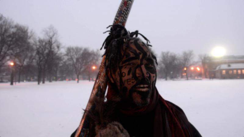 portrait winter park snow african american man dreadlocks facepaint charcoal no slaves didgeridoo