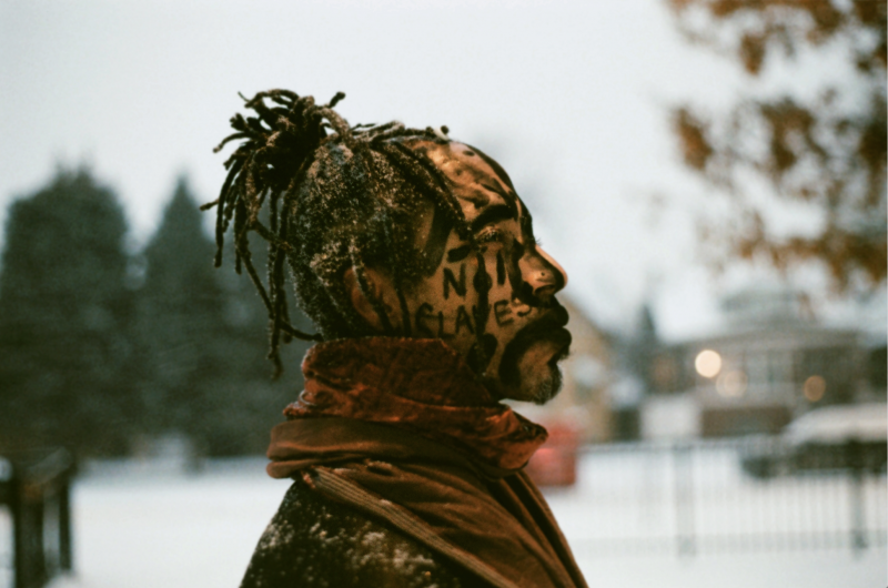 portrait winter park snow african american man dreadlocks facepaint charcoal no slaves didgeridoo