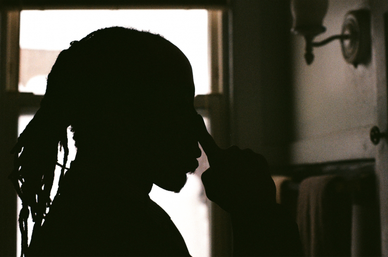 silhouette bathroom mirror man touching face dreadlocks shadow