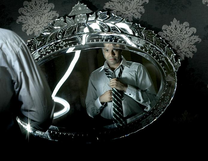 digital photograph light portrait dark light contrast chiaroscuro mirror ornate oval flash streak reflection young african american black man adjusting striped tie white button down shirt wallpaper baroque fleur de lis pattern