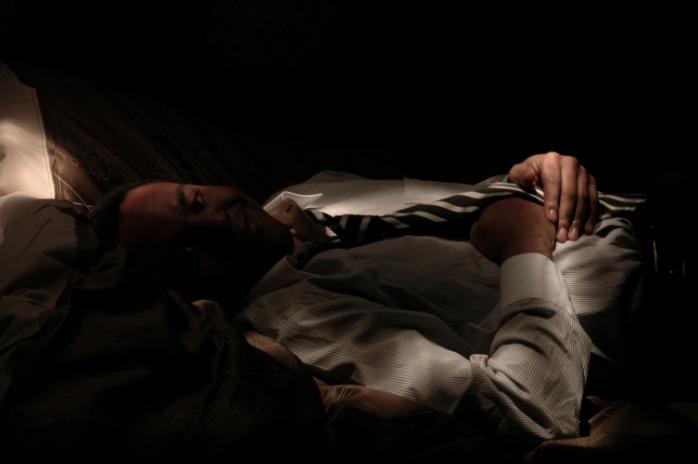 light portrait digital photograph dark light chiaroscuro black white striped tie necktie shirt button down lying down bed young african american black man hand holding under strange weird shadows creepy