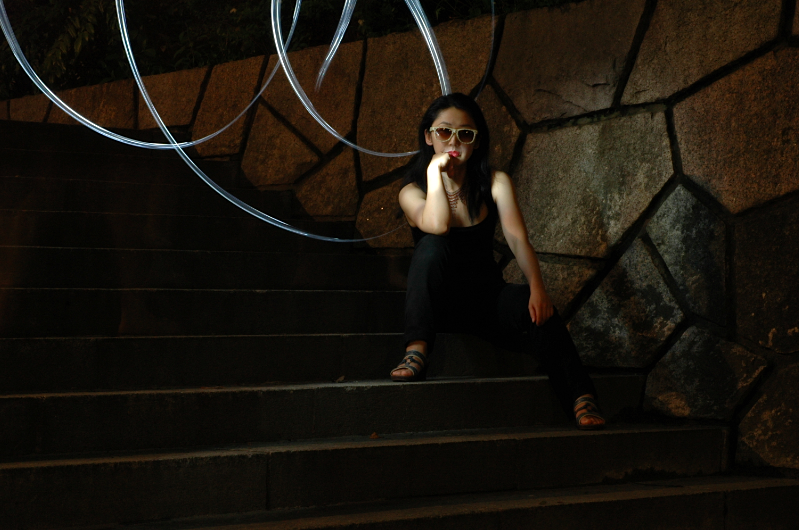 photograph digital light portrait dark shadow contrast chiaroscuro streak blur glow flash highlight young asian woman japanese sitting stone steps moss white black polka dot sunglasses hand chin jeans sandals reflective impatient pensive attitude cool