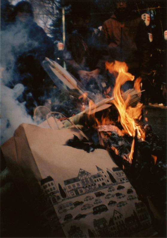 "film photograph of burning paper bags and ""hamaya"" arrows japan japanese traditional new year's day ritual purification old new paper bag licking flame smoke rising curling dark chiaroscuro lomography composition vintage"
