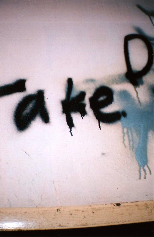 film photograph of graffiti on a wall glare white drip bright
