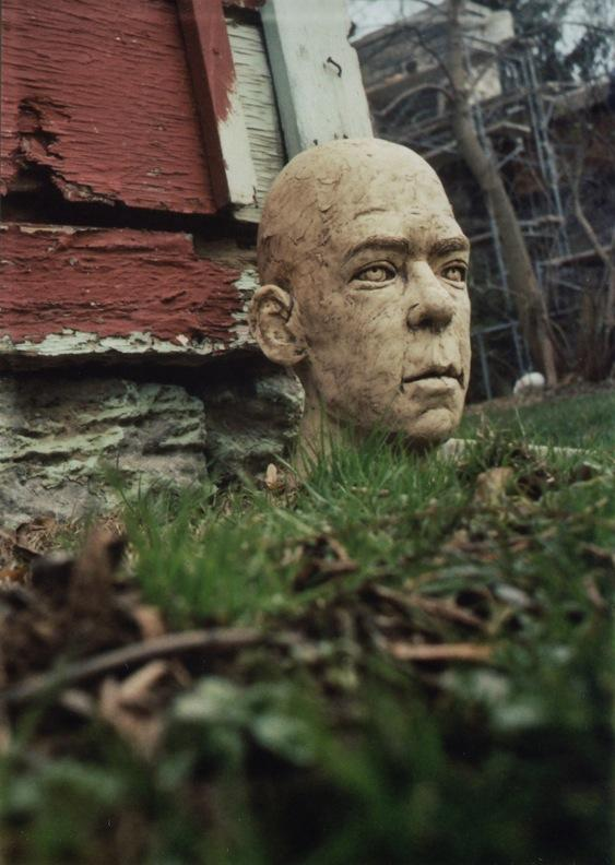 photograph of a sculpture of a head on the lawn creepy menacing disembodied severed empty eyes peeling old deserted haunted barn red building lawn closeup strange weird creepy surreal halloween