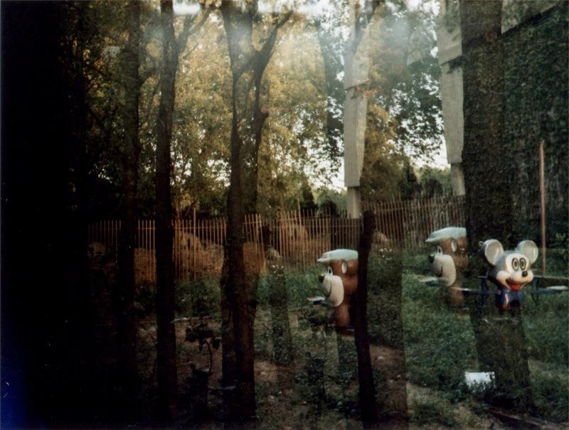 film photograph of trees and playground equipment double exposed exposure lomography light play falling dark chiaroscuro strange bizarre surreal magritte style interlacing interlocking composition nature children toy bizarre weird pretty