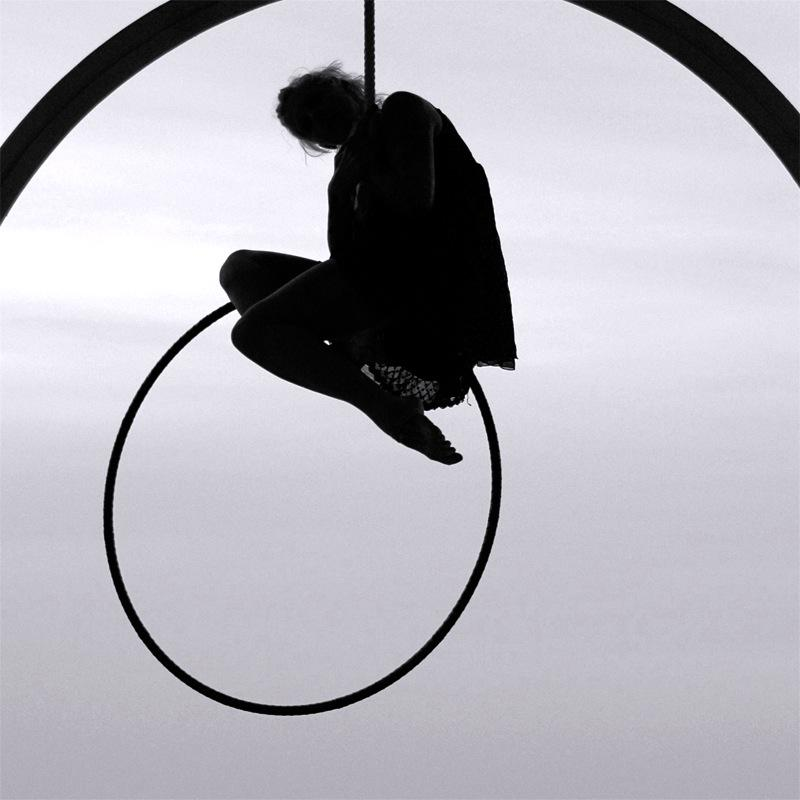 photograph of a girl posing on an aerial ring hoop lyra circus  shadow silhouette
