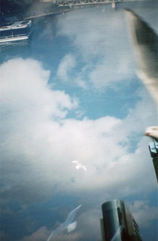 film photograph of sky, trees, birds, buildings, and boat lomography exposure double multiple flying soaring blur birds boat water sky highrises downtown surreal composition