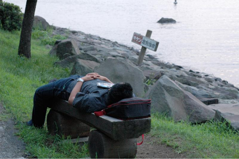 photograph of a man sleeping on a bench at the seashore (rocky)
