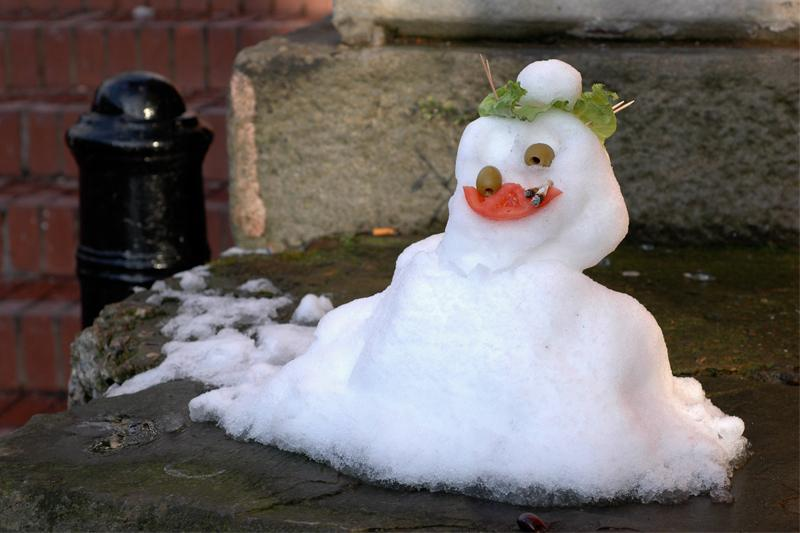 a snowman with tomato mouth olive eyes, lettuce hair and a cigarette butt funny grin lopsided eyeball falling out silly grotesque gross bizarre surreal sad