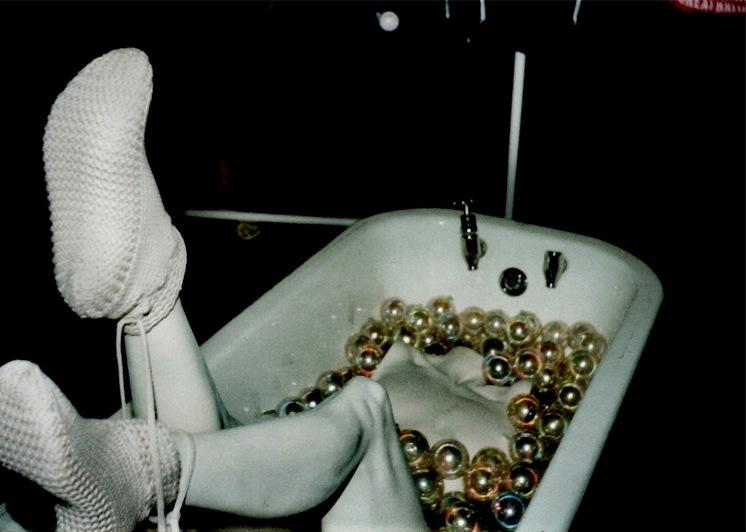 film photograph of white legs coming out of a bathtub filled with gold balls flash contrast jarring strange surreal bizarre weird knit boots booties sneakers naked headless armless black white party christmas ornaments bubbles no arms head