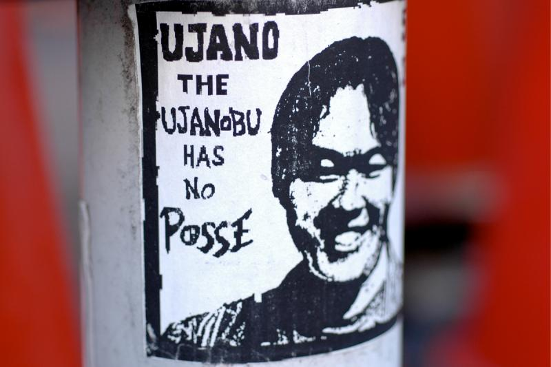 photograph of a graffiti sticker on a pole strange japanese posse japanglish funny weird