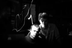 light portrait photography long exposure black white chiaroscuro contrast lighting streak flash two young men boys blond beard bunker shelves strange mysterious