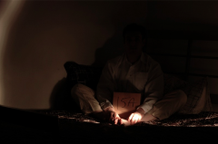 dark shadowy photograph man boy sitting brown cardboard box on bed darkness flash light streaky portrait grainy hidden face mysterious strange weird pajamas black white
