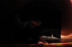 dark black light portrait white flash streak lighting blurry mysterious man boy  bare feet naked hunched hugging knees carpet in fireplace hiding