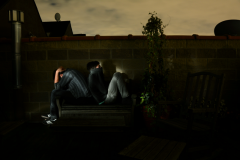 light portrait digital photograph chiaroscuro contrast dark shadow lighting rooftop wall brick plant lawn furniture deck two young men boys bench sitting holding head sweater over mouth tired despair surreal sky weird