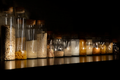 light portrait digital photograph dark light chiaroscuro contrast reflection streak line glass jars kitchen counter rice pasta oatmeal beans quinoa flakes cork stopper row perspective shorter different heights shiny set old-fashioned