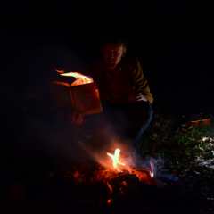 digital photograph young man brown jacket jeans outdoors crouching reading book flames fire on flaming burning campfire bonfire guitar mandolin dark night
