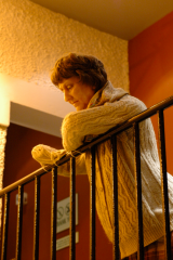 digital photograph middle aged old lady woman sweater leaning over railing short haircut cropped pensive looking down missing hand mannequin creepy surreal uncanny valley realistic wax figurine