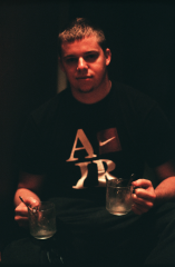 film photograph young man holding two empty glasses spoons portrait