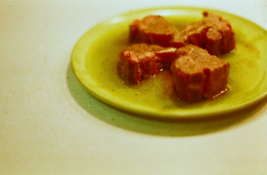 film photograph yellow green plate meat steaks raw glistening marinade bokeh