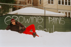 film photograph vintage retro winter snowbank graffiti fence growing pains of the soul young man reclining red pants funny