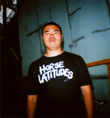 "film photograph of a man in a tshirt reading ""horse latitudes"" strange surreal portrait vintage blurry bad english japanglish funny bizarre lustig droll belligerent inimical square heavyset"