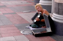 photograph of a woman sitting on the sidewalk and playing the accordion busker tiles pillars blonde tan suitcase money