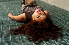 young woman girl model brunette wavy hair lying back grate grating vent