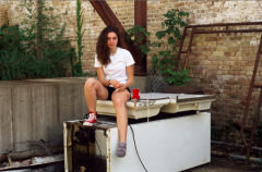 film photograph portrait young woman sitting old broken abandoned fridge tying shoes