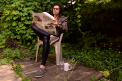 digital photograph portrait garden chair white plastic reading newspaper young man leather pleather pants tights