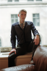 film photograph portrait young man blond proper tie button down shirt office leather chair vest intense gaze