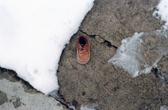 film photograph snow winter sidewalk baby shoe abandoned