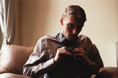 film photograph portrait young man blond proper tie button down shirt office tying