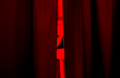 film photograph red filter young man curtain gap peeking through