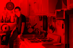 film photograph red filter young man sitting portrait kitchen stovetop range burner