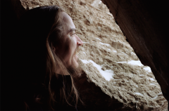 film photograph portrait bearded young man long hair looking out cave rocks snow winter smiling laughing