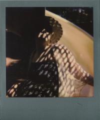 polaroid color portrait sunlight chiaroscuro shadow dapple pattern pretty spots young woman sun hat sunglasses playground slide