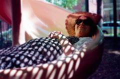 film photograph portrait young woman bokeh dreamy lying slide maternity sunglasses sunlight dappled