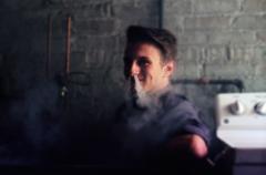 bokeh film photograph portrait young man smoke nostrils dragon smile exhale vape